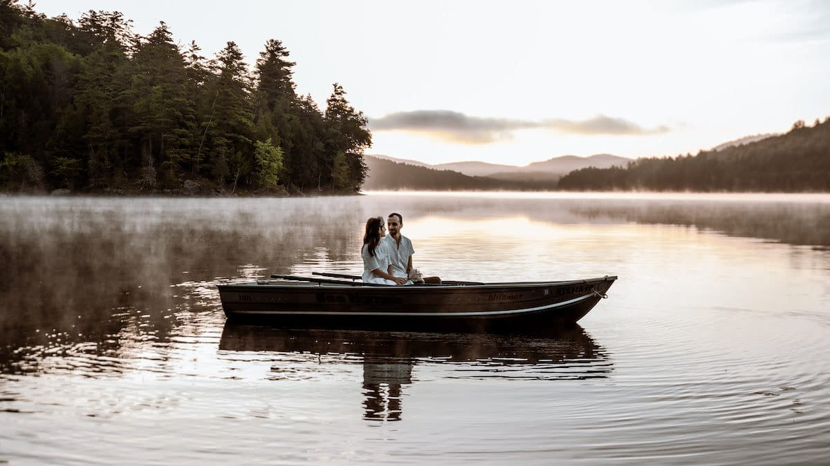 Couple eloping on Paradox Lake near Schroon Lake, New York at sunrise in a row boat