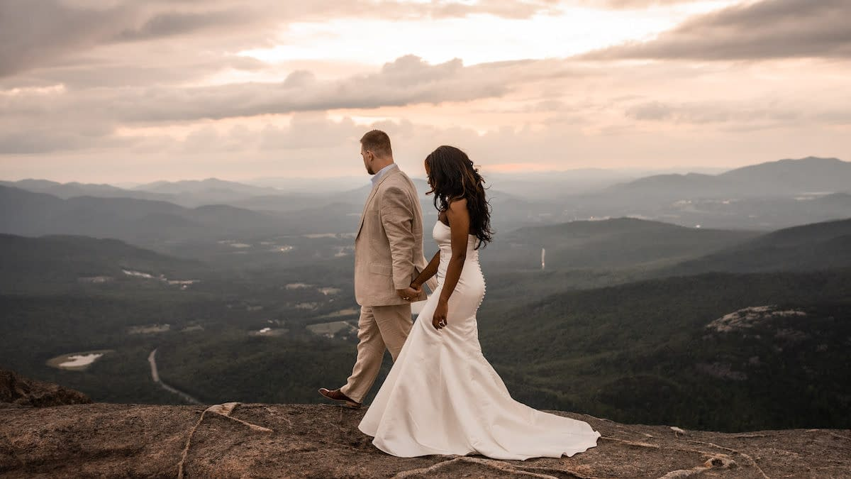 Couple eloping on Cascade Mountain in Lake Placid, New York at sunset overlooking the Adirondack Mountains