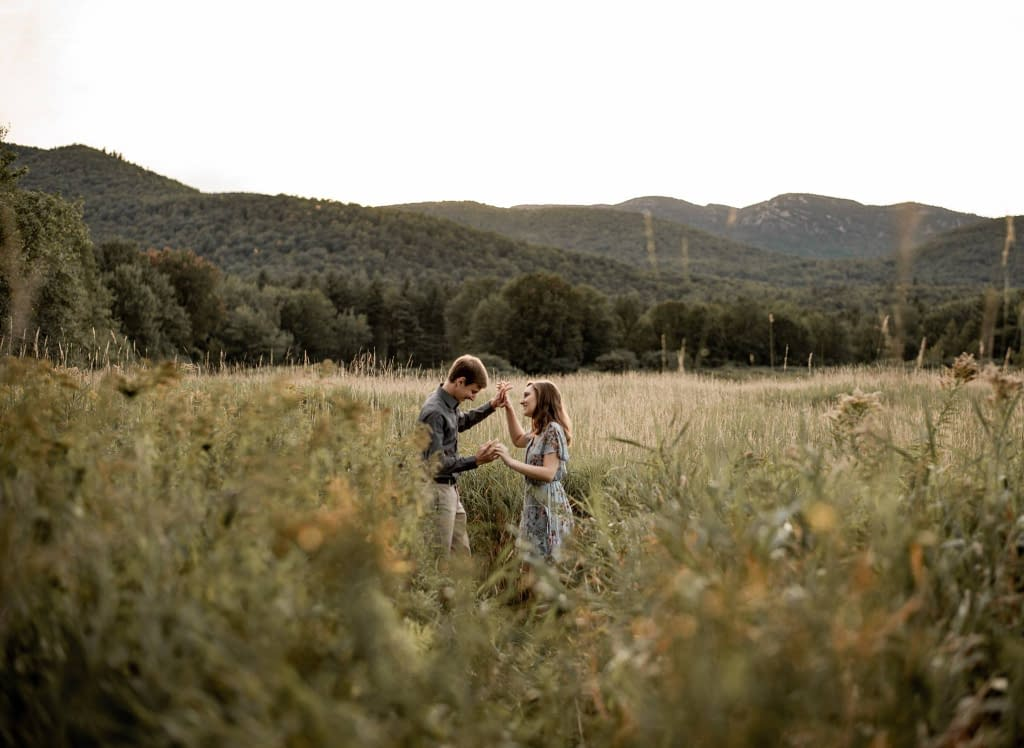 Engagement photos in a field near the high peaks of the ADKs