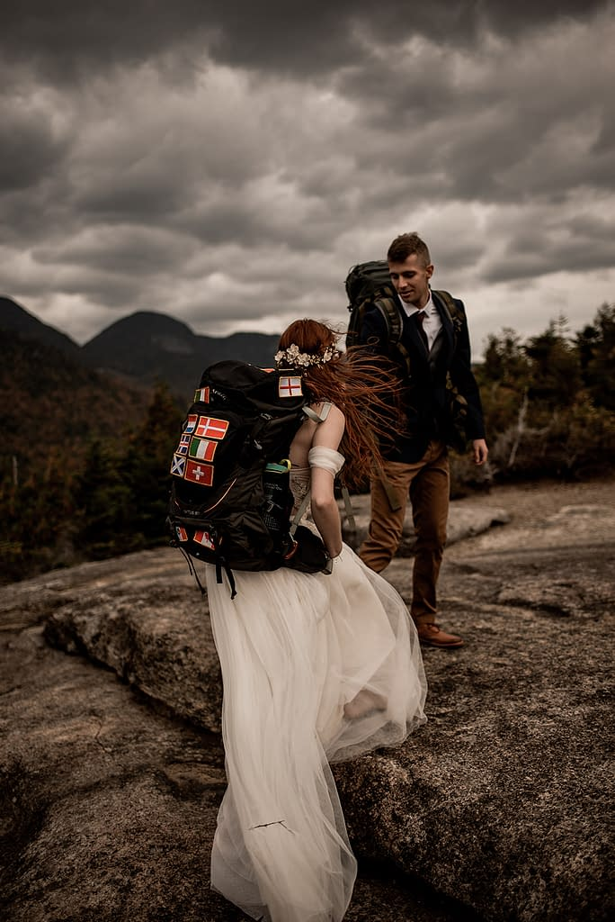 Bride and groom hiking in backpacks for a mountaintop elopement